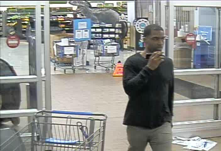 black male in black long sleeve shirt with tan pants, talking on cell phone - Suspect 2